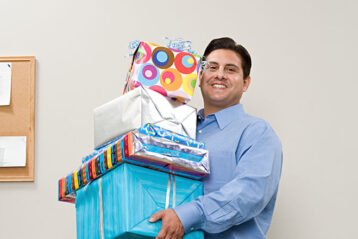man carrying lot of gift boxes