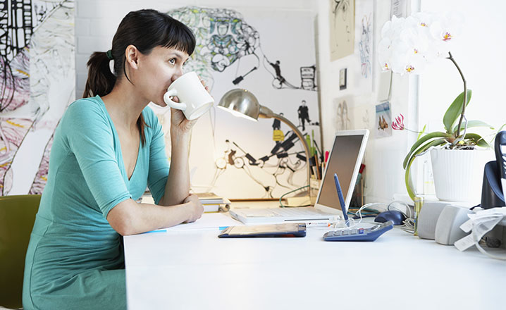 woman drinking coffee in the office