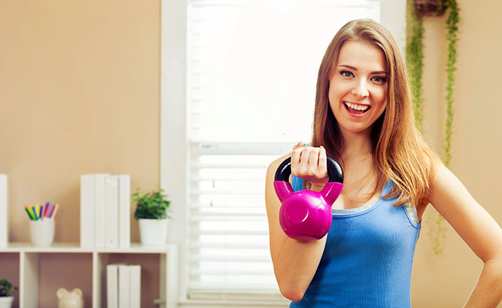 young woman working out with a kettlebell